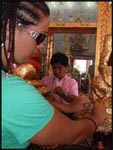 Placing a piece of 24 carrot gold paper onto a buddah at the temple to bring good luck